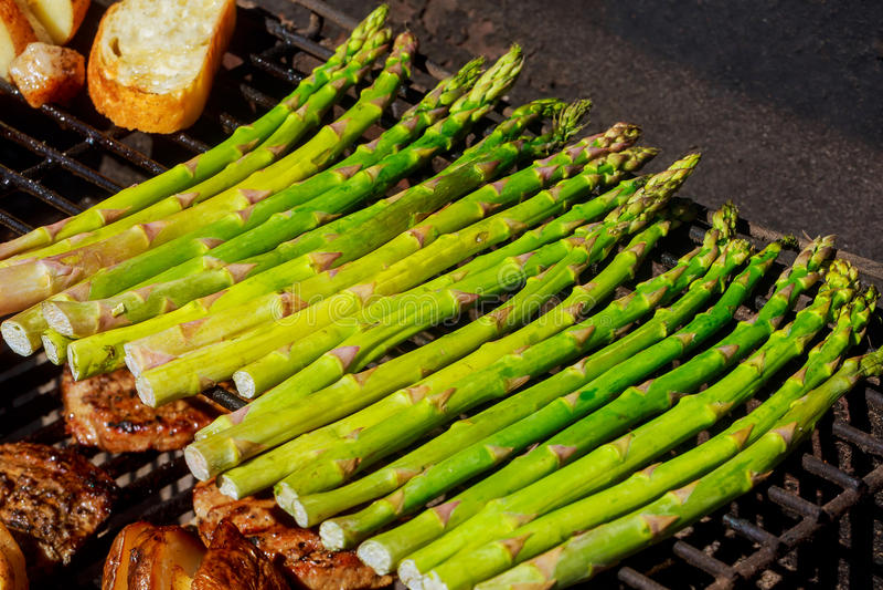 De sappige varkenskoteletten worden geroosterd op rooster met asperge en groene paprika Binnenplaats het roosteren stock afbeelding