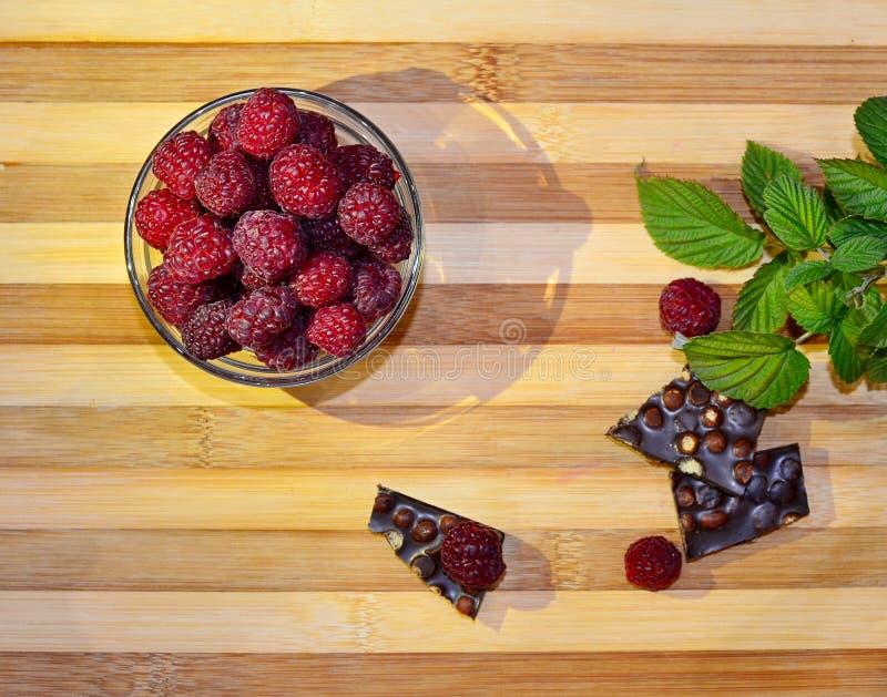 De sappige verse frambozenbessen liggen in een kom en op een lijst met groene bladeren en stukken van chocolade, de hoogste menin royalty-vrije stock foto