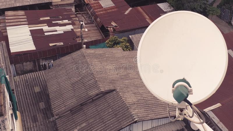 De satellietschotelopstelling op de bovenkant van de bouw onder de roestige krottenwijken van zink matal oude daken royalty-vrije stock fotografie