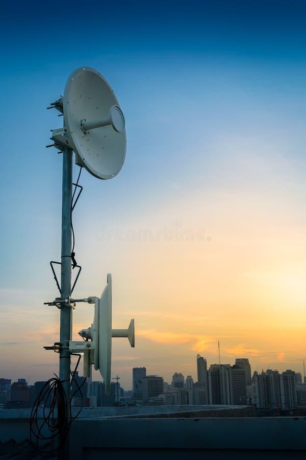 De satellietschotelsantennes, signaal communiceren op het dak van het gebouw stock afbeelding