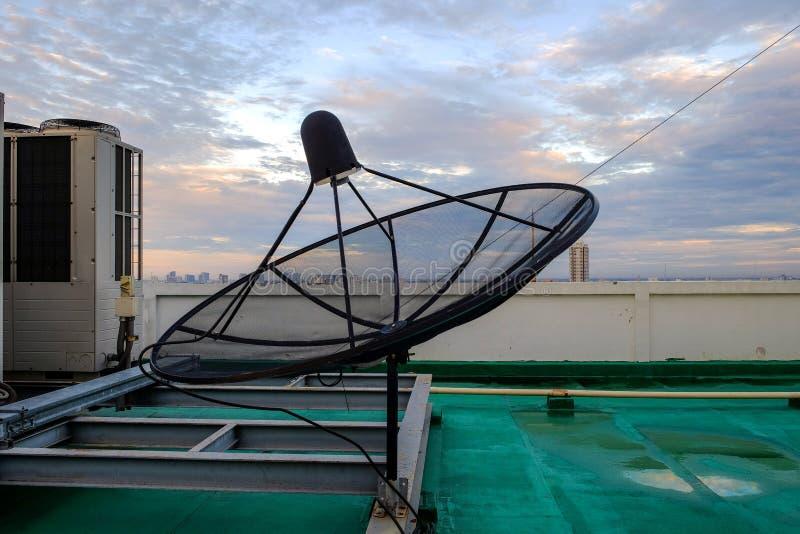 De satelliettribune van de schotelontvanger op het dak van het gebouw stock fotografie