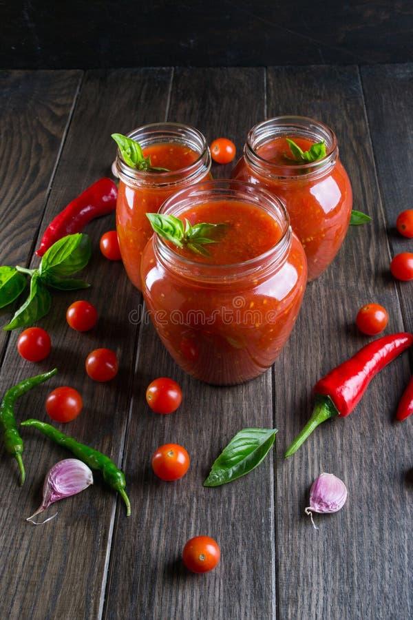 De saus van de tomatenketchup met kersentomaten en roodgloeiende Spaanse peperpeper, knoflook en kruiden in een glaskruik op donk royalty-vrije stock afbeelding