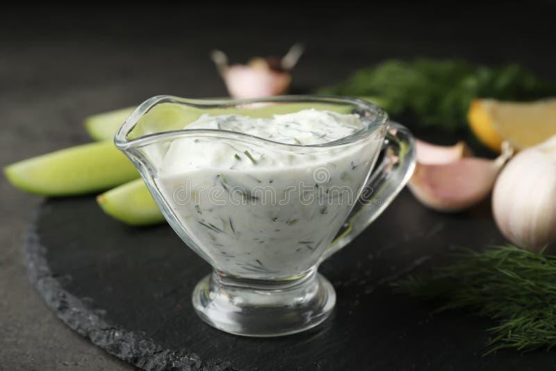 De saus van de Tzatzikikomkommer in glaswaterkruik met ingrediënten royalty-vrije stock foto's