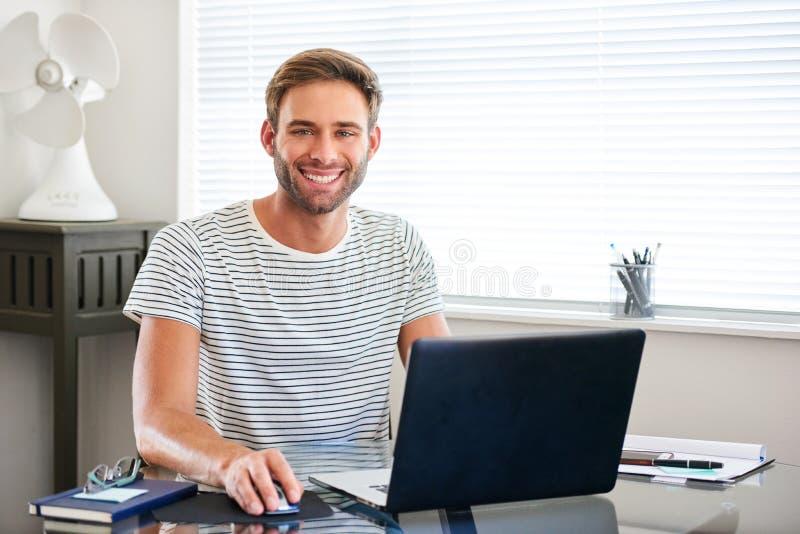 De savvy jonge mens die van technologie bij camerazitting glimlachen achter computer stock foto