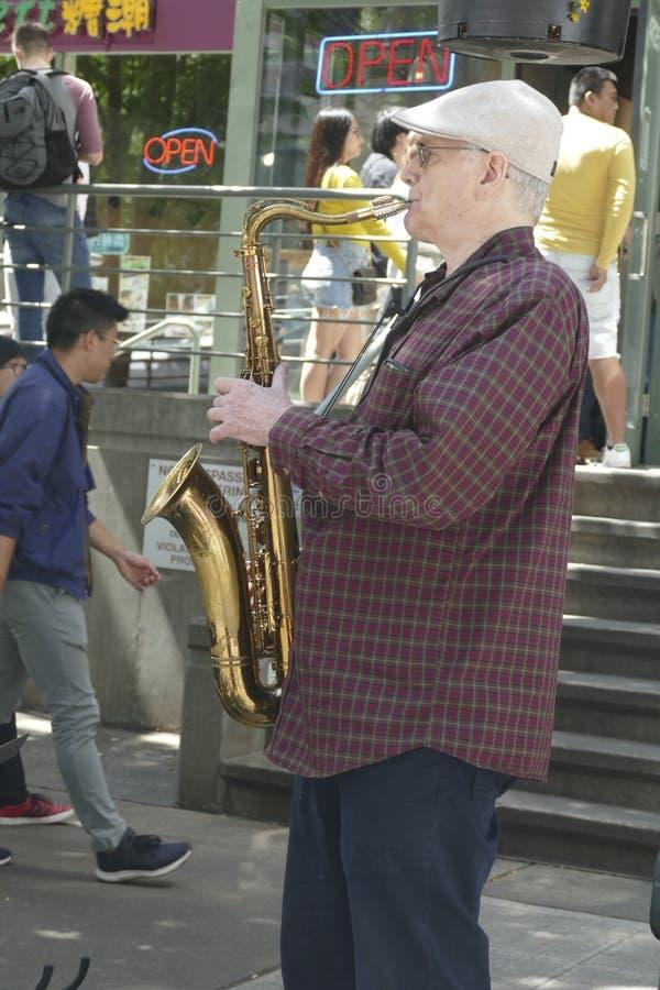 De Saxaphonekunstenaar speelt jazz bij de 50ste Jaarlijkse Universitaire Markt van de Districtsstraat royalty-vrije stock foto