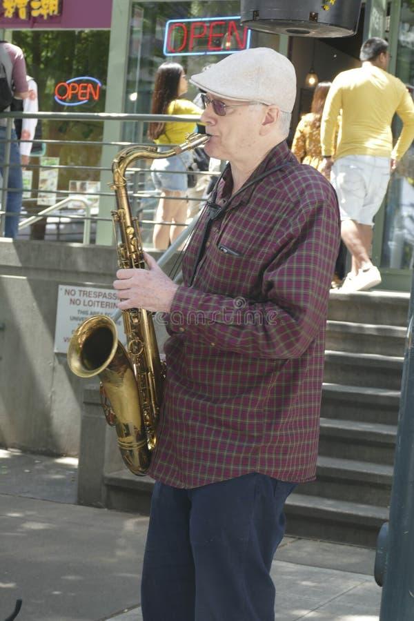 De Saxaphonekunstenaar speelt jazz bij de 50ste Jaarlijkse Universitaire Markt van de Districtsstraat royalty-vrije stock afbeeldingen