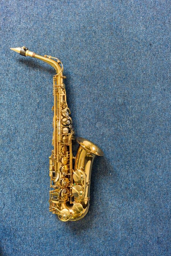 De saxofoon van Golden van de jazzmusicus op blauwe muur stock afbeelding
