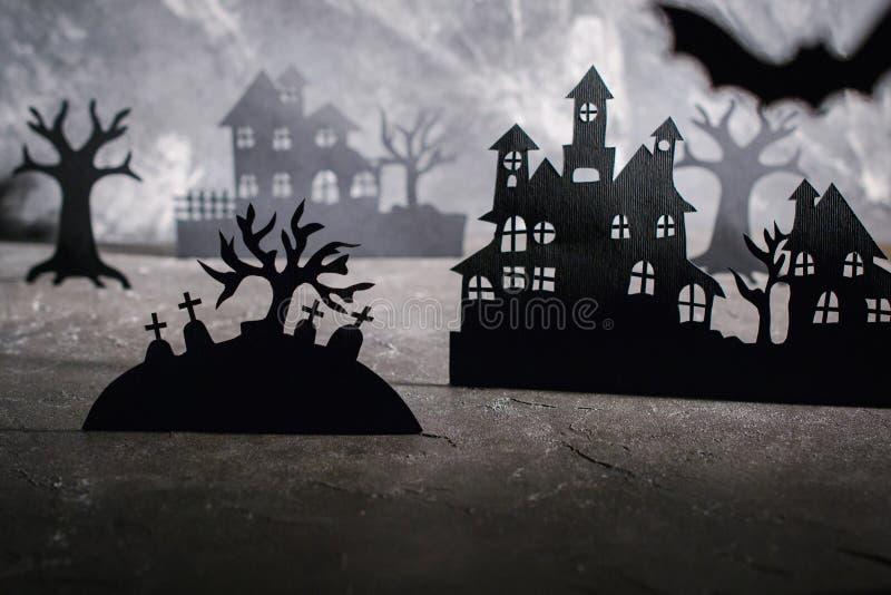 De scène van Halloween Document huizen en donkere nevelige bomen in kerkhof royalty-vrije stock fotografie