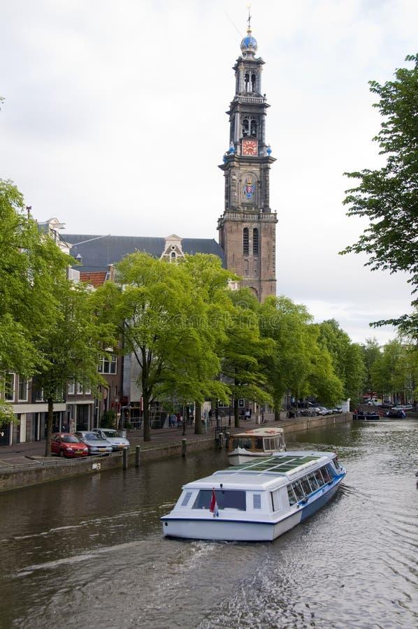 De scène van het kanaal met toeristenboot westekerk Amsterdam stock foto's