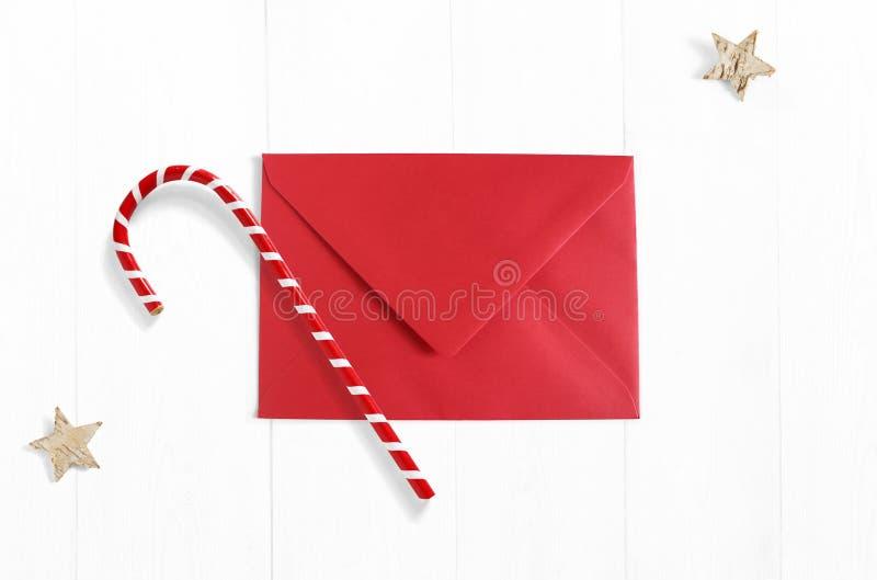 De scène van het Kerstmismodel met rode die envelop, de decoratie van het suikergoedriet en sterren van berkeschors op witte hout royalty-vrije stock afbeelding