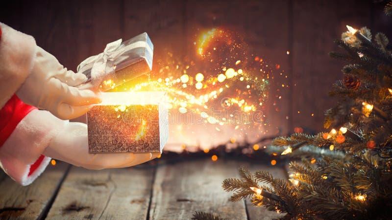 De scène van Kerstmis Santa Claus-het openen doos met magische gift stock foto