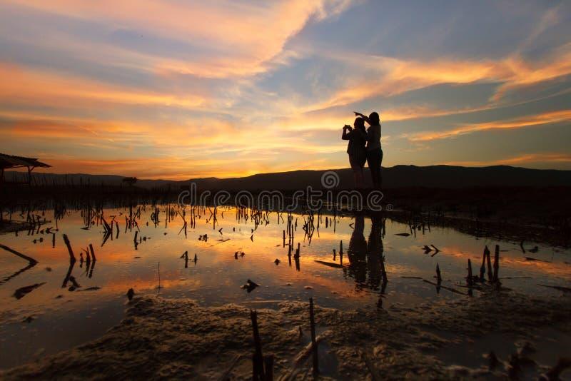 De scène van de landschapsaard van vrouwen die de foto schieten bij dramatische hemel stock afbeeldingen