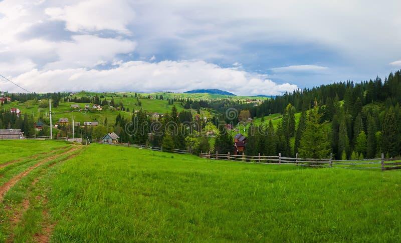De scène van de lentebergen met houten gespleten spooromheining over een groen en weelderig weiland, een landweg en oude huizen o stock foto