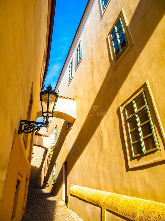 De scène van ochtendpraag Zonovergoten en lange schaduwen op de muur met gasstraatlantaarn, Thunovska-Straat, Lesser Town, Praag royalty-vrije stock fotografie