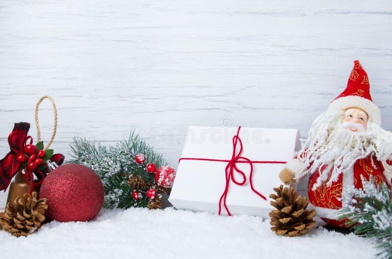 De scène van de winterkerstmis met Kerstboomtakken, decoratie, speelgoed en Santa Claus op sneeuw en houten achtergrond, stock foto's