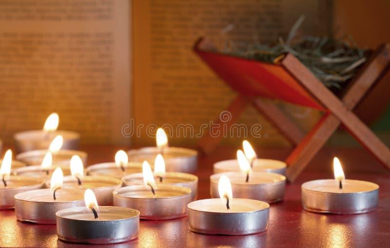 De scènekaarsen en bijbel van de troggeboorte van christus op nacht abstracte achtergrond stock foto
