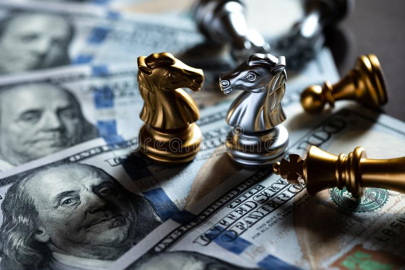 De schaakridders bevinden zich tegen elkaar op Amerikaanse dollarbankbiljet De bedrijfsconcurrentie en strategieconcept royalty-vrije stock afbeeldingen