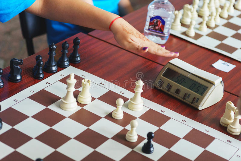 De schaakspeler klikt op de chronometerknoop terwijl het spelen van een spel van schaak royalty-vrije stock foto