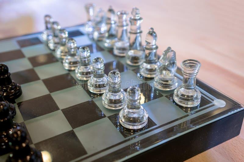 De schaakstukken op de raad tijdens het spel, schaak maakten van glas stock foto's