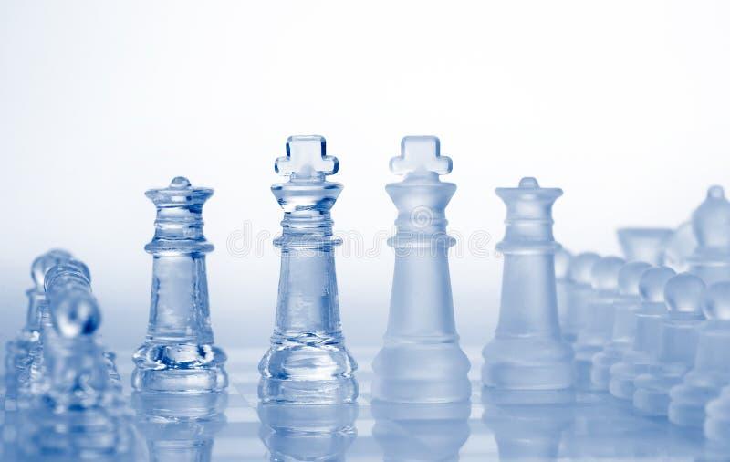 De schaakstukken van het glas met blauw licht royalty-vrije stock afbeelding