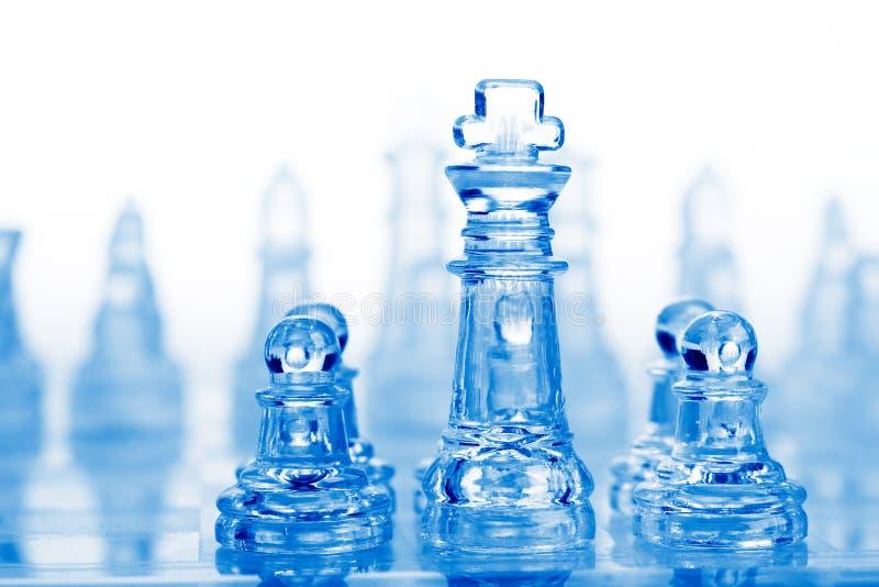 De schaakstukken van het glas met blauw licht stock fotografie