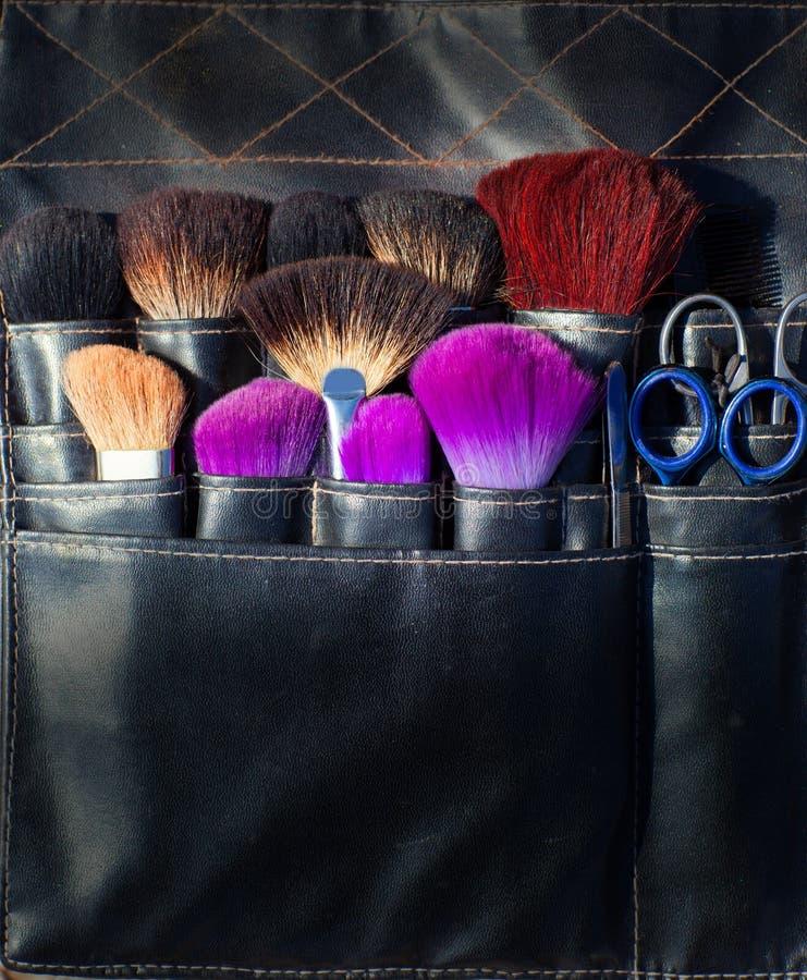 De schaar van borstels en hulpmiddelen van make-upkunstenaar in zwarte stock afbeelding