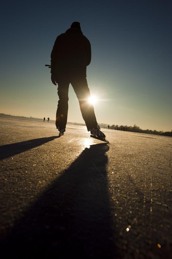 De schaatser van het ijs bij zonsondergang stock afbeeldingen