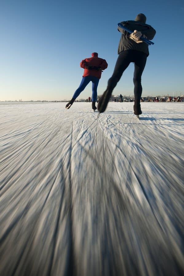 De schaatsers van het ijs op een bevroren meer. royalty-vrije stock fotografie