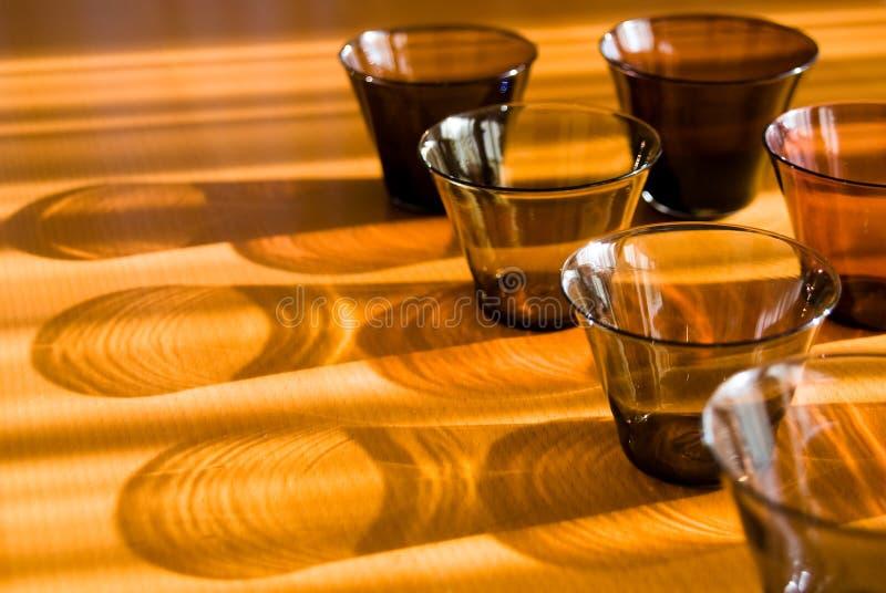 In de schaduw gestelde glazen op de houten lijst. stock afbeeldingen