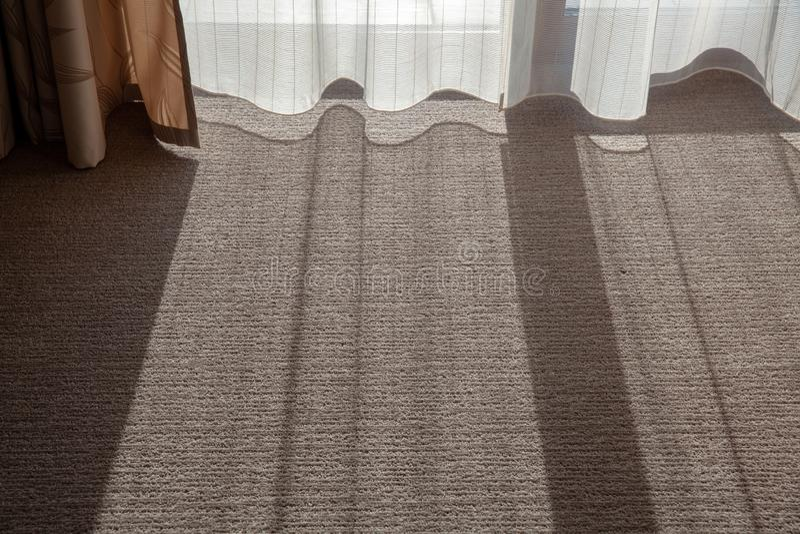 De schaduw op het tapijt in de ruimte De zon glanst door de gordijnen in de ruimte stock foto's