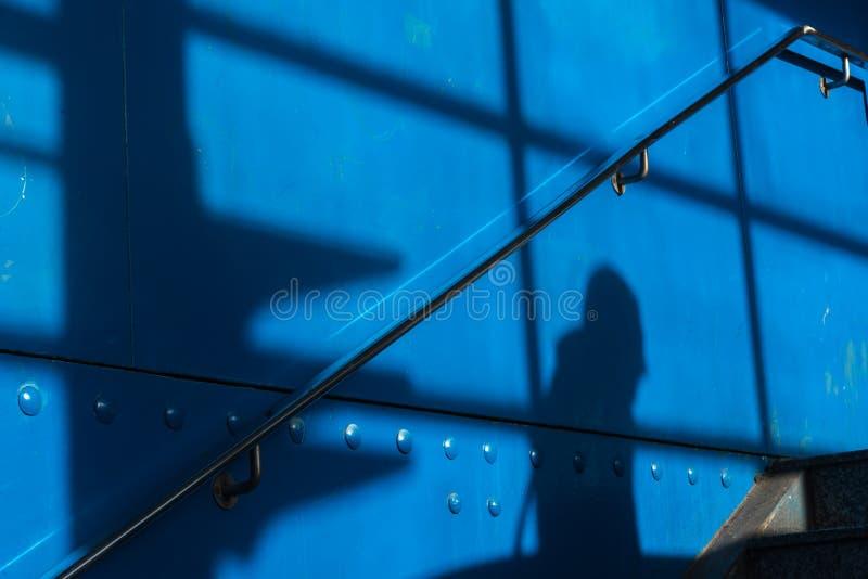 De schaduw van een mens op een blauwe oppervlakte royalty-vrije stock afbeelding