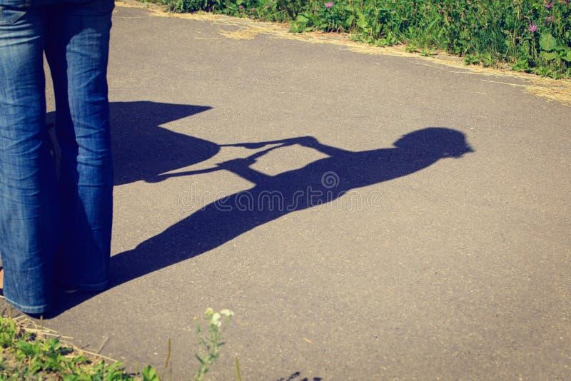 De schaduw van het moederschapconcept van de jonge wandelwagen van de moederholding stock fotografie