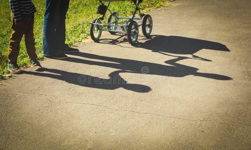 De schaduw van het moederschapconcept van jonge moeder die weinig zoon en wandelwagen houden royalty-vrije stock foto