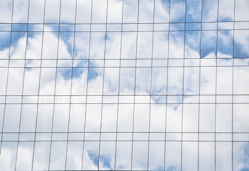 De schaduw van het wit betrekt en blauwe hemel op het duidelijke glas van de de bouwmuur royalty-vrije stock afbeelding