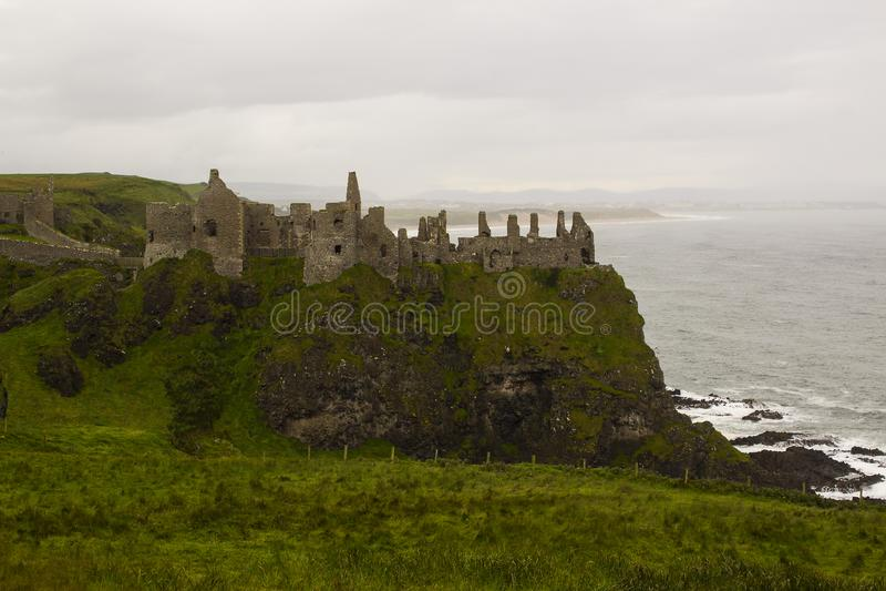 De schaduwrijke ruïnes van het middeleeuwse Ierse Dunluce-Kasteel op de klippenbovenkant die de Atlantische Oceaan in Ierland ove stock foto