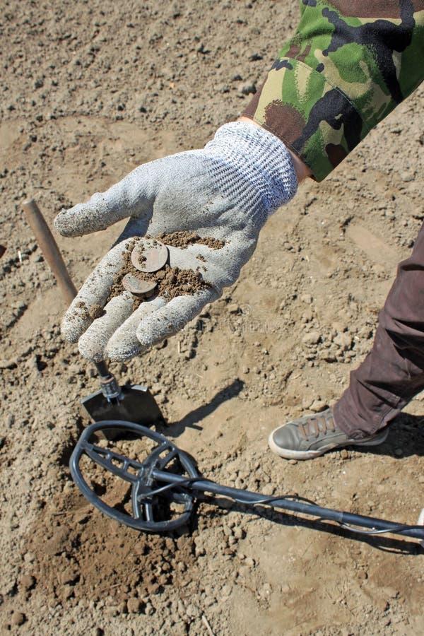 De schat-jagers Het werken met een metaaldetector stock afbeelding