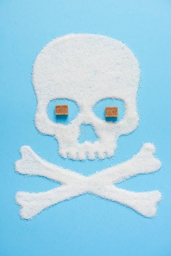 De schedel van suiker op blauwe blauwe achtergrond wordt gemaakt die Het concept van de diabetes Suikerdoden Het voorstellen van  stock afbeelding