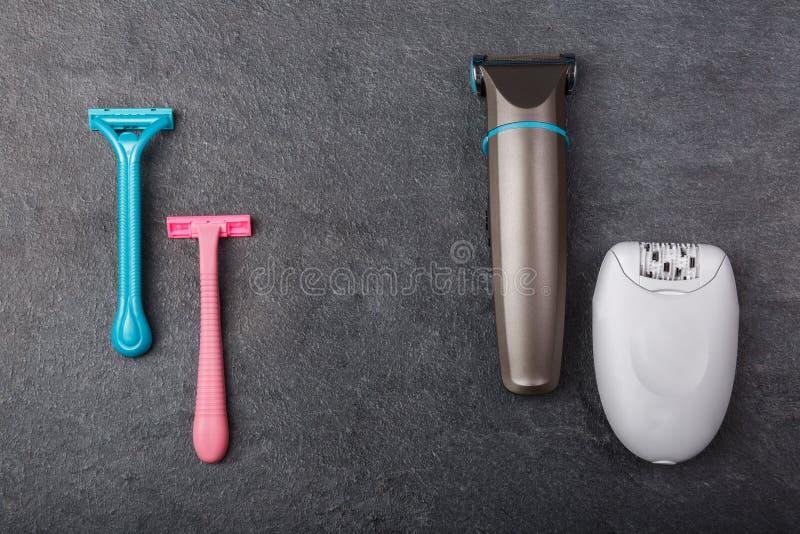 De scheermessen, een depilator en een snoeischaar zijn op een grijze achtergrond stock fotografie