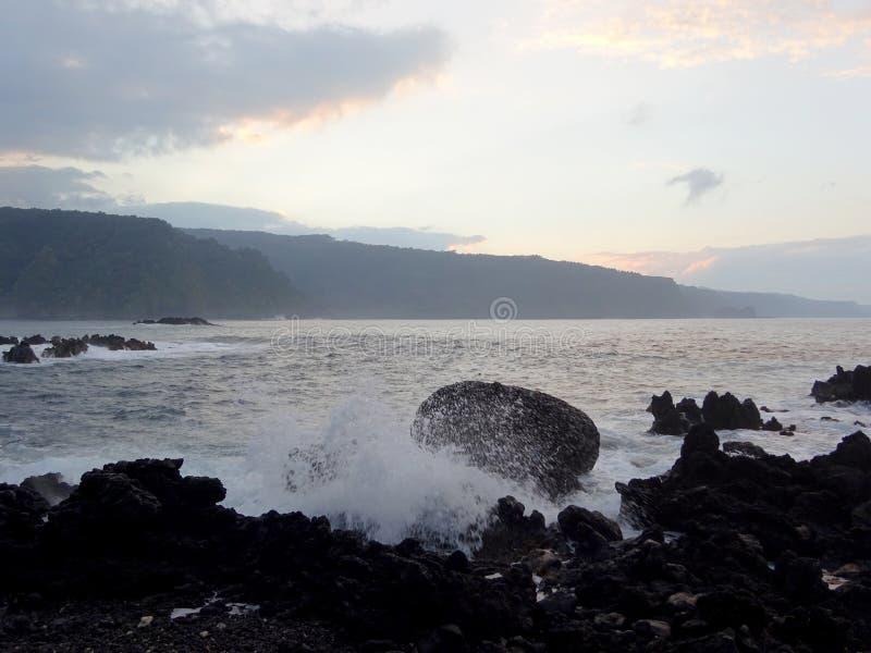 De schemer langs Rocky Shore met golven verplettert langs rotsen en wolken in de hemel royalty-vrije stock fotografie