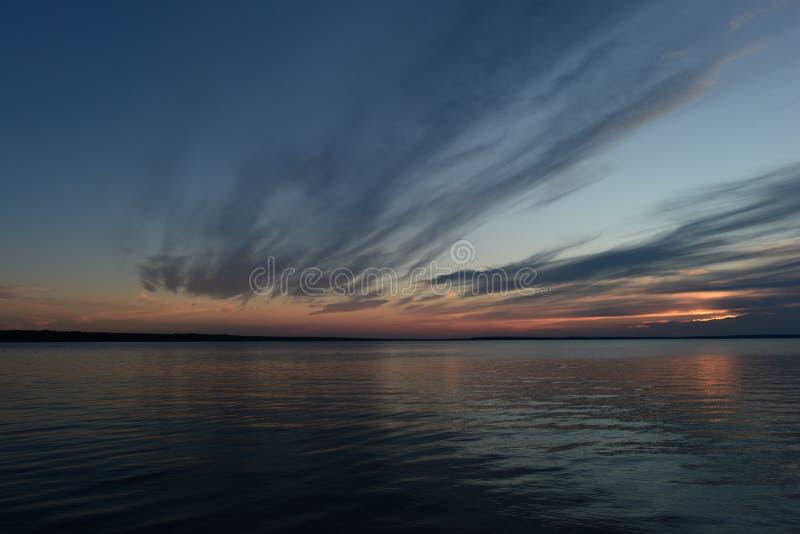 De schemeringhemel in de gloed van zonlicht van de wolken overdacht de waterspiegel van het meer stock afbeeldingen