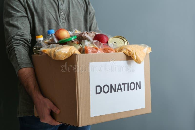 De schenkingsdoos van de mensenholding met voedsel op grijze achtergrond stock afbeelding