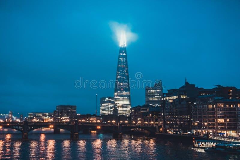 De Scherfwolkenkrabber bij Nacht helder wordt verlicht die royalty-vrije stock afbeeldingen