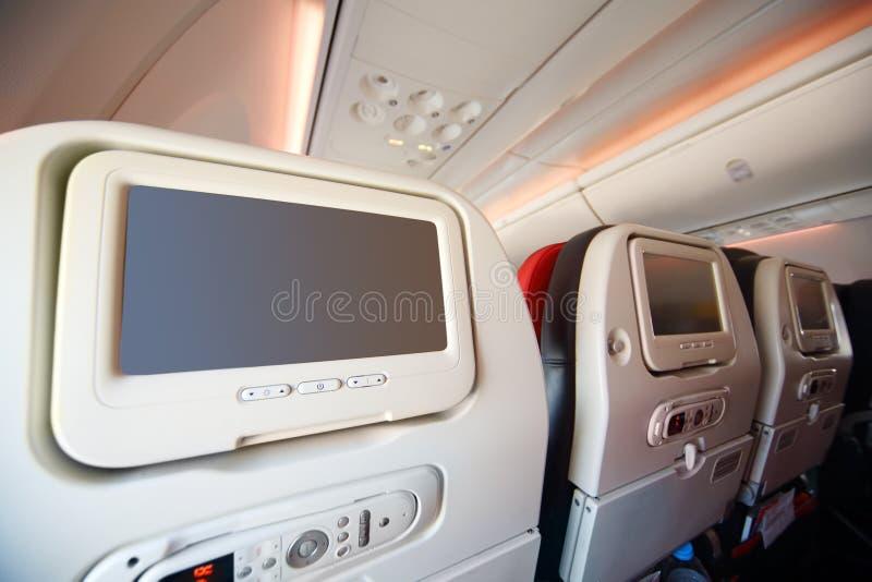 De schermen voor passagiers in rug van zachte zetels in vliegtuig. stock afbeelding