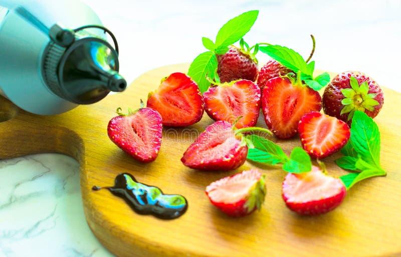 De scherpe aardbeien op een houten raadsfles met chocolade verglazen en muntbladeren royalty-vrije stock afbeeldingen
