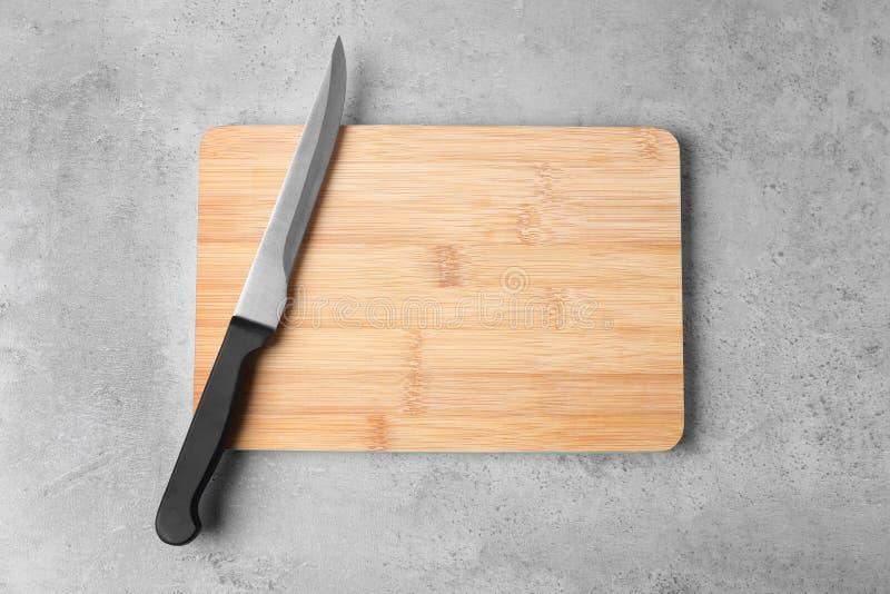 De scherpe raad met mes op grijze vlakke achtergrond, legt stock afbeeldingen