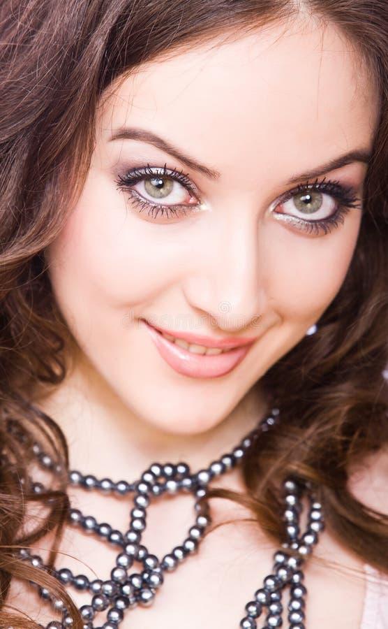 De schichtige glimlachende jonge vrouw met is royalty-vrije stock foto's