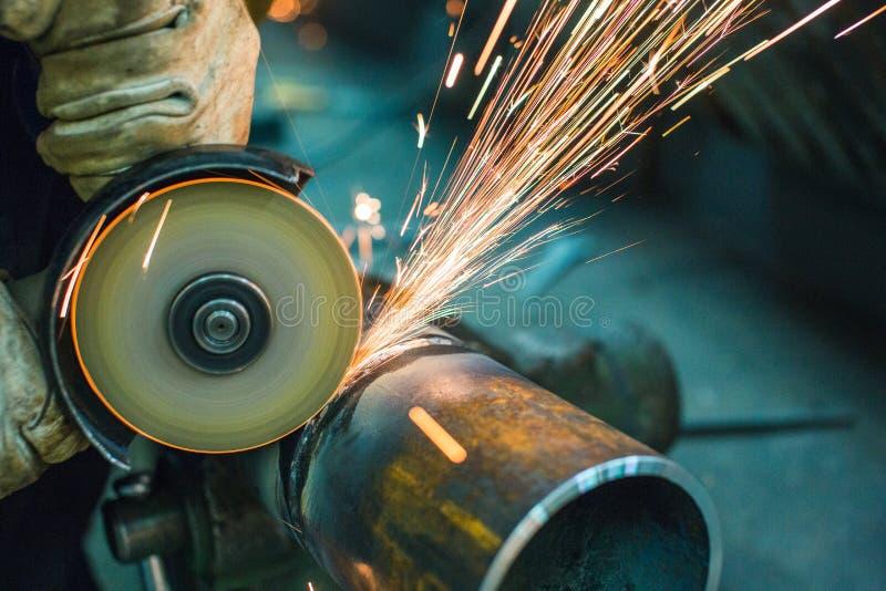 de schijf snijdt een stuk van staalpijp met af een malende machine in een metaalfabriek royalty-vrije stock afbeeldingen