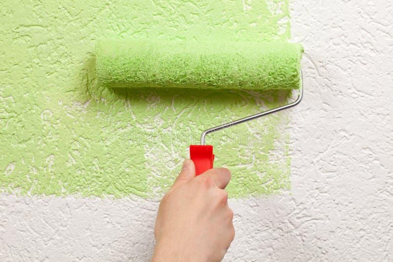 De schilder schildert een muur met een verfrol stock fotografie