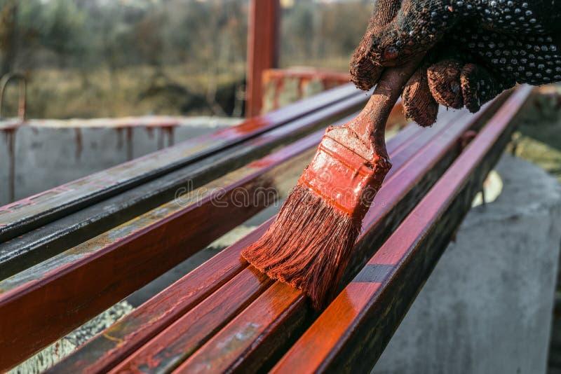 De schilder schildert metaalstructuren Beschermende deklaag van staal gesloten profielen met het rood van het inleidingsijzeroxid royalty-vrije stock foto