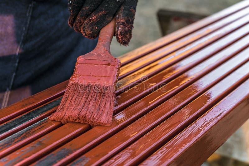 De schilder schildert metaalstructuren Beschermende deklaag van staal gesloten profielen met het rood van het inleidingsijzeroxid stock foto's